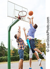 group of happy teenage friends playing basketball - summer...