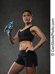 woman drinking water from bottle in gym - fitness, sport,...