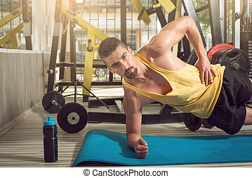 Man doing side plank exercise in gym