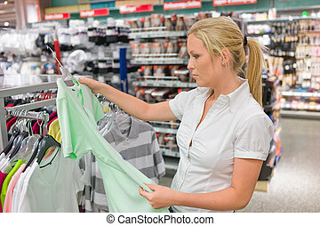 woman buying clothing - a young woman buying clothing in...