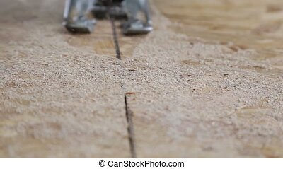 Close up electric jigsaw cutting a piece of wood - Sawing...