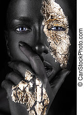 fashion portrait of a dark-skinned girl with gold make-up....