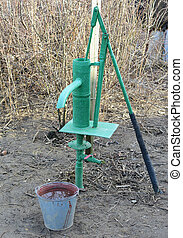 Hand pump leading to an artesian well. Pumping water for...