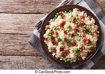 Couscous salad with green peas and pomegranate horizontal...