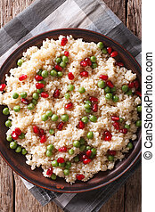 couscous with pomegranate close-up vertical top view -...