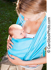Mother with newborn baby in sling - Mother carrying her...