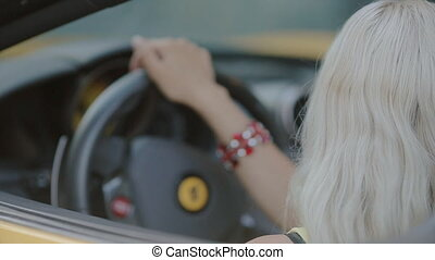 Blonde in sits behind the wheel of cabriolet - Blonde in...