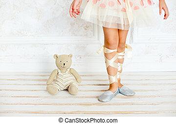 the girl the ballerina with a teddy bear - feet of the...
