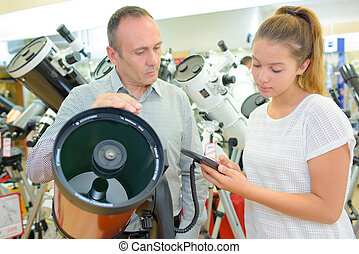 Man and young lady in telescope shop