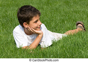 smiling boy - a boy is smiling on the green grass
