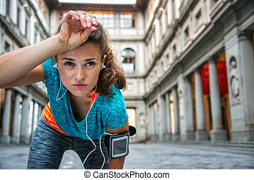 Young woman in sportswear is catching breath - Now it is...