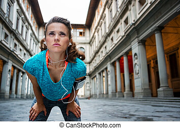 Sporty woman catching breath in front of Uffizi gallery -...