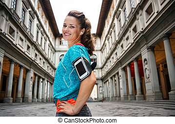 Portrait of smiling fitness woman with mp3 player, Florence...
