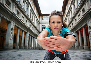 Sportswoman with headset is stretching - Now it is time to...