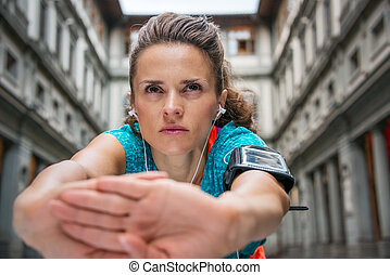Close up on sporty young woman with earphones stretching -...