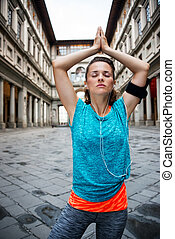 Fitness young woman with earphones doing yoga outdoors - Now...