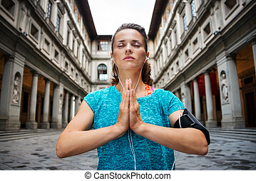 Young fitness woman in sports outfit is doing yoga. Florence...