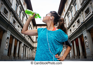 Sporty woman with headset is drinking water from the bottle...