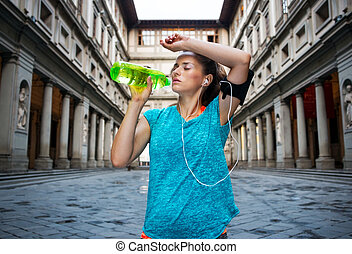 Fitness woman is drinking water while outdoors training -...