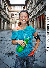 Young smiling sporty woman with bottle of water. Florence -...