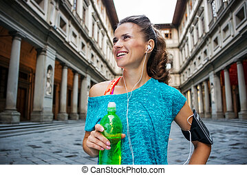 Portrait of happy fitness woman with bottle of water...