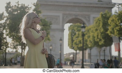 Charming blonde posing near the Arc de Triomphe in Paris