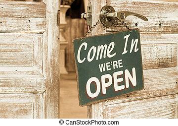 Come In We're Open on the wooden door open. Vintage retro...