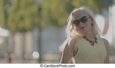 Charming woman in sunglasses posing in Paris in summer