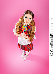 Teen girl in school uniform posing over pink background....