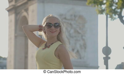 Happy girl posing near the Arc de Triomphe in Paris