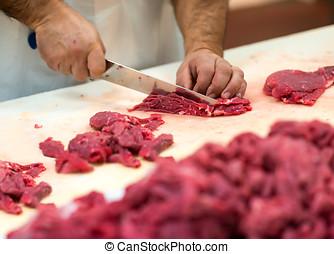 Hands preparing cuts of raw meat