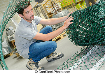 Man unrolling fencing wire