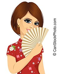 Chinese woman in traditional Cheongsam dress holding a fan