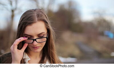 Beautiful girl with glasses smiling at the camera -...