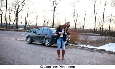 Business girl speaks by phone in the yard near the car HD