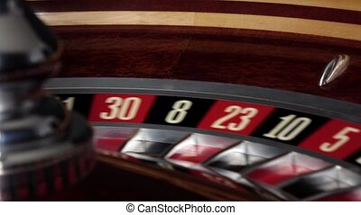 Usual roulette wheel running with white ball, side view -...