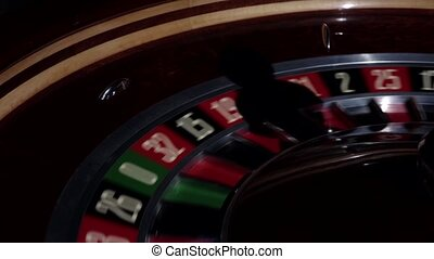 Usual roulette wheel running with fallen white ball, shadow,...