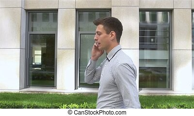 Attractive businessman speaking on the phone while walking along modern building, slow motion