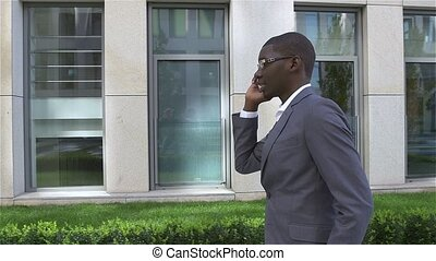 American Businessman talking on cell phone, standing in front of his office. slow motion