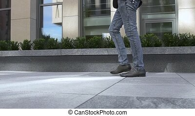 Human foot with brown leather shoes and jeans, slow motion -...
