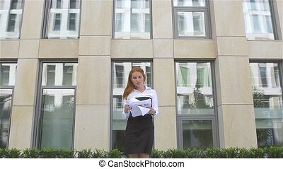 young business woman with papers flying up, slow motion