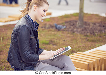 Smiling woman surfing the net on fresh air