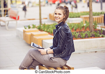 Smiling woman on a bench surfing the net