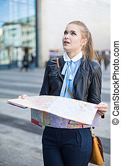 Confused woman with map in city