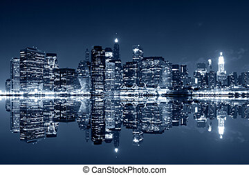 Manhattan at night with reflections on Harlem river -...