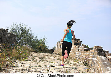 young fitness woman trail runner running at chinese great...