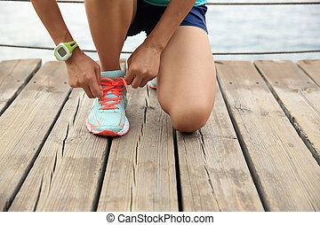 sports woman runner tying shoelace on wooden boardwalk...