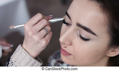 A cute model gets makeup put on before her shoot. Close up...