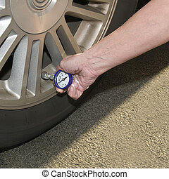 Low tire pressure - Woman checking her tire pressure to help...