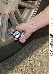 Low Pressure - Woman checking her tire pressure to help...